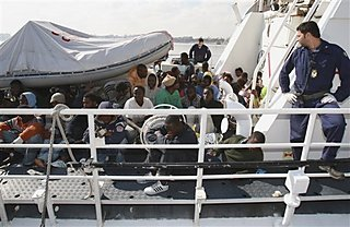 Rescued migrants are seen at an Italian coast guard boat while arriving at the port of Tripoli